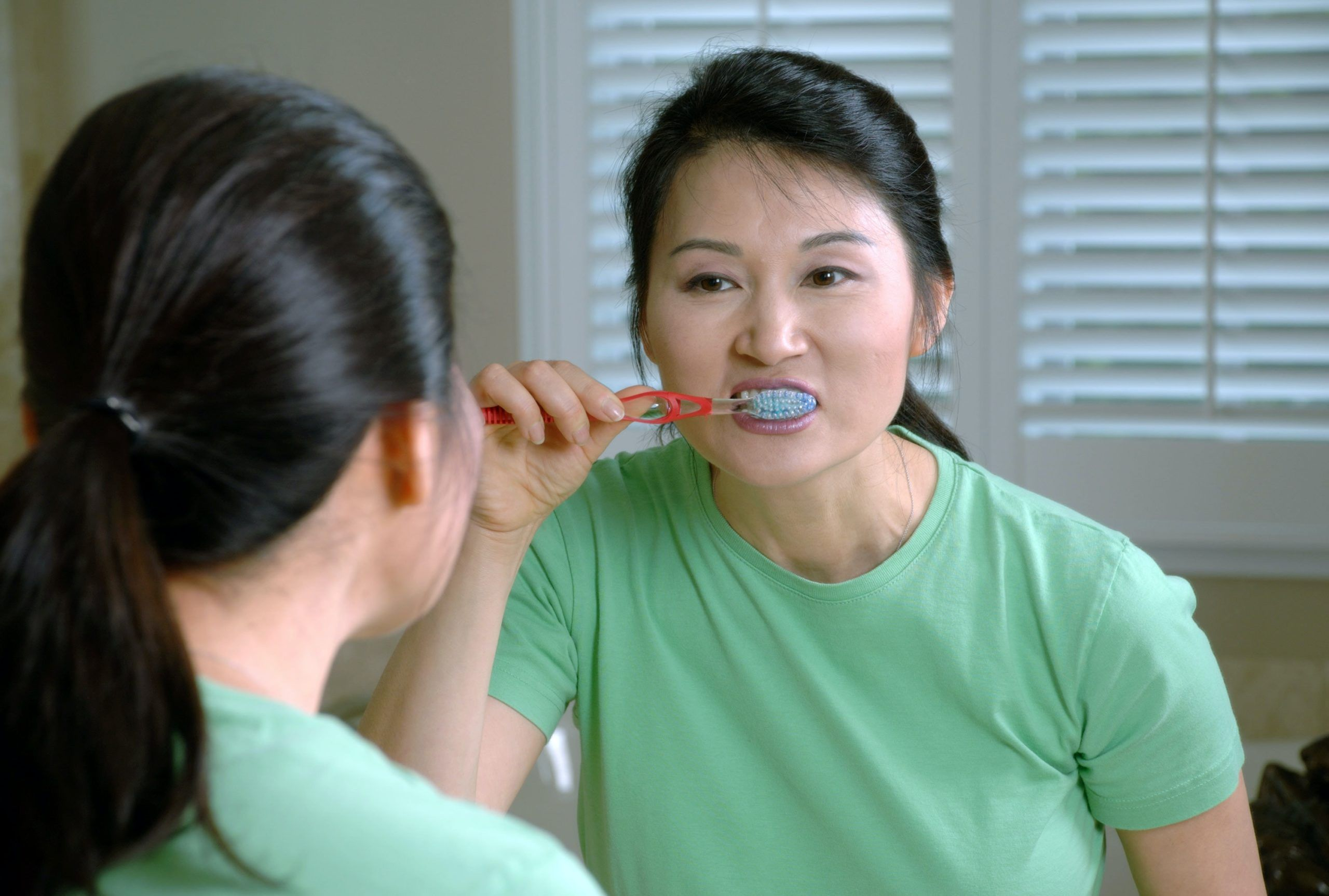 woman-brushing-teeth-with-mirror